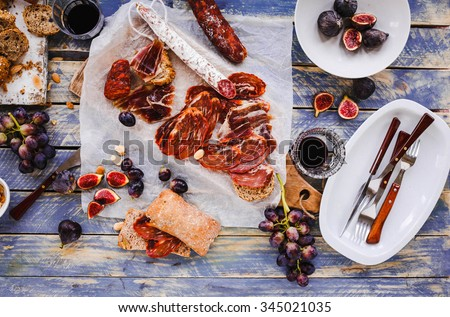 Antipasti and fruit concept. Tasting gourmet party on a rustic wooden table. A quick and easy snack for party time. Rustic style - stock photo