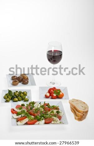 antipasti misti and bread on white plates - stock photo