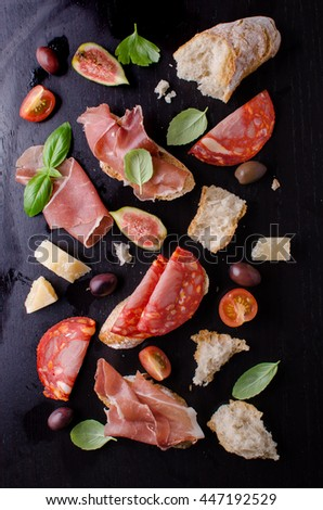 Antipasti on black - prosciutto, salami, bread, cheese and basil on black background