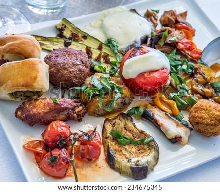 Antipasti on white plate ay Italian restaurant. - stock photo