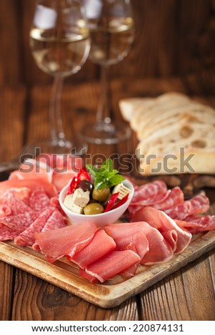 antipasti Platter of Cured Meat,   jamon, olives, sausage, salami,  ciabatta and white wine glasses on textured wooden table - stock photo