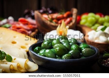 Antipasto and catering platter with different meat and cheese products - stock photo