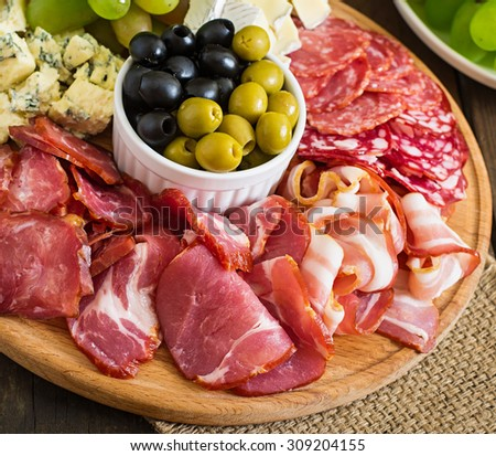 Antipasto catering platter with bacon, jerky, salami, cheese and grapes on a wooden background - stock photo