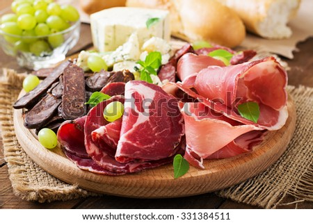 Antipasto catering platter with bacon, jerky, sausage, blue cheese and grapes on a wooden background - stock photo