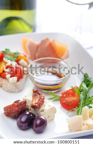 Antipasto; olives and sundried tomato, parma ham with rock melon, toast with roasted mixed peppers and feta cheese, cubes of cheese and salad - stock photo
