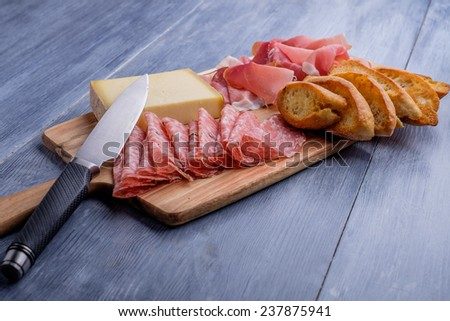 Antipasto plate with cheese salami and ham - stock photo