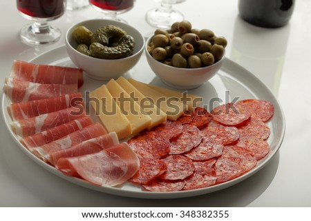 Antipasto with cured meat, sausage, cheese, green olives, and pickles - stock photo