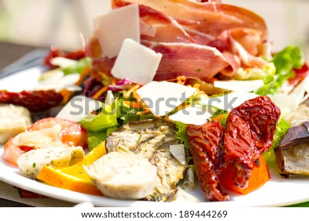 antipasto with ham, parmesan cheese, fish and dried tomatoes - stock photo