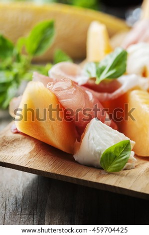 Antipasto with melon, mozzarella, ham and basil, selective focus