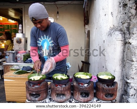 "ANTIPOLO CITY, PHILIPPINES - MARCH 23, 2016: A food vendor cooks ""bibingka"", a local delicacy made of glutenous rice topped with egg, along the streets of Antipolo City, Philippines - stock photo"