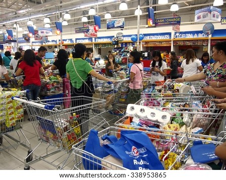 ANTIPOLO CITY, PHILIPPINES - NOVEMBER 3, 2015: Customers line up with their shopping cart to pay for their items in a grocery in Antipolo City in the province of Rizal, Philippines. - stock photo