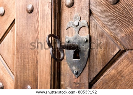 antique aged key in strong wooden door - stock photo