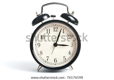 Antique alarm clock in black metal over white background - stock photo