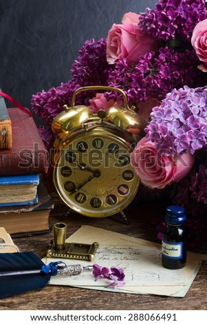 antique alarm clock, pile of mail with blue feather pen - stock photo