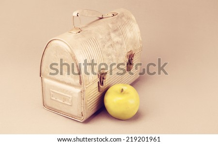 Antique aluminum lunch box against gray background with apple.  - stock photo