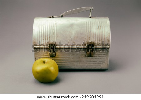 Antique aluminum lunch box against gray background with apple. Analog filter.  - stock photo