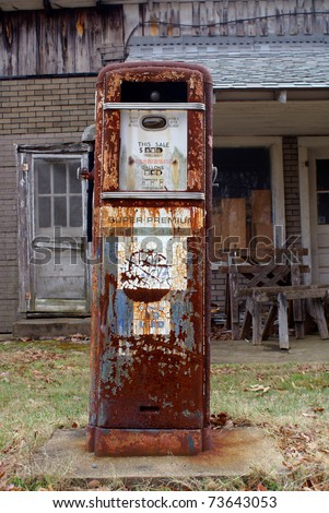 Antique American gas pump. Rusted and with chipped off paint in front of a old brick building. Logos & brand names are removed. - stock photo