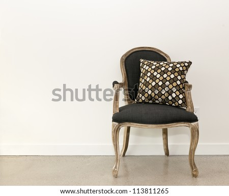 Antique armchair furniture with cushion against white wall - stock photo