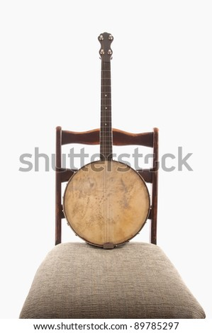 Antique banjo  on antique armless upholstered chair, white isolation.