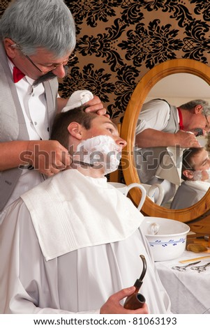 Antique barber shaving a customer the old-fashioned way - stock photo