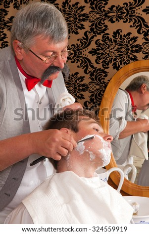 Antique barber shaving a customer with shaving cream - stock photo