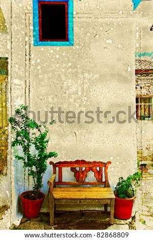 Antique bench against a wall with pot plants next to it with texture background and space for text in Turkish village of Sirince.