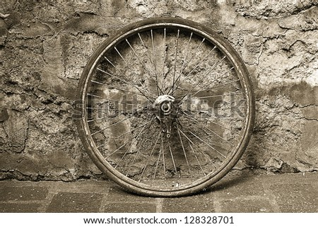antique bicycle wheel isolated against old wall background. - stock photo