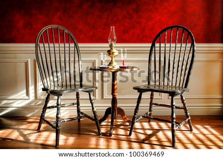 Antique black Windsor style chairs and mahogany table with glasses and oil lamp in an early American colonial decor historic home interior parlor with decorative wall molding and faux finish red paint - stock photo