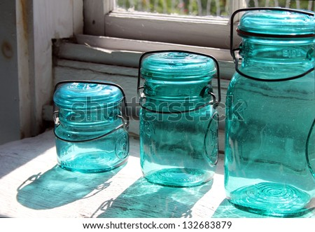Antique blue canning jars with reflection sitting on old wood table - stock photo