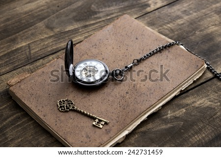 Antique book and pocket watch on grunge wooden table, close up - stock photo