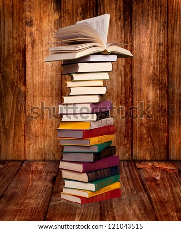 Antique book stack with open book on the top isolated on wooden background - stock photo