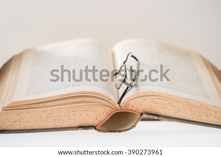 antique book with glasses isolated, selective focus - stock photo