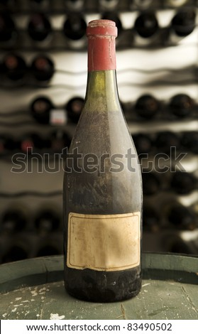 Antique bottle of wine, with an old blank label, on top of a wine vat in a cellar. This is known as a museum class wine. - stock photo