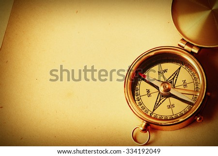 Antique brass compass over old map background   - stock photo
