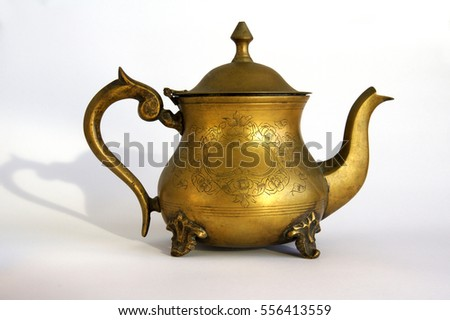 Antique brass teapot with a pattern on white background with shadows