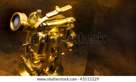 Antique brass theodolite shot on textured brown background with space for copy