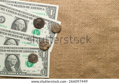 Antique bronze coins  with portraits of emperors and banknotes on cloth