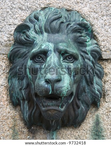Antique bronze lion mask fixed to a granite block wall