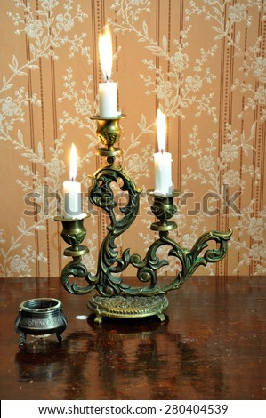 Antique candelabra with three melting candles on an old wallpaper background - stock photo