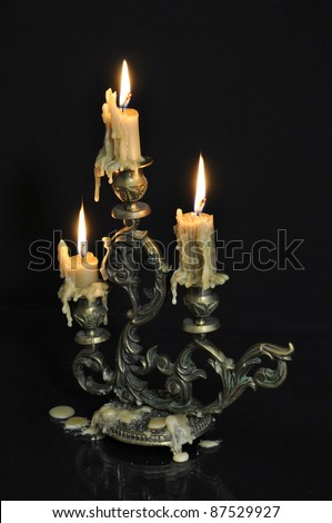Antique candelabra with three melting candles on black background - stock photo
