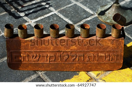 Antique  candlestick for Hanukkah holidays.Simple form, rusty metal, hebrew letters.Jerusalem flea market. - stock photo