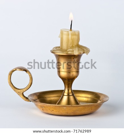 antique candlestick with a burning candle on white background