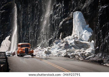 Antique car on a mountain road covered with crushed glacier - stock photo