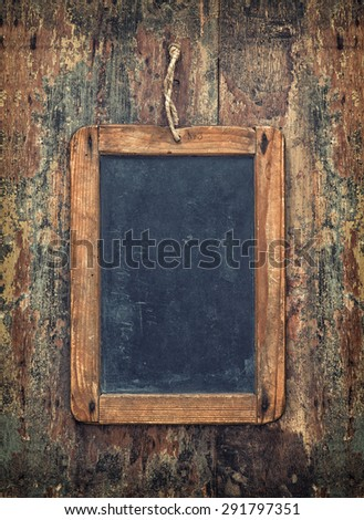 Antique chalkboard on wooden texture. Rustic background with copy space for your text. Vintage style toned picture - stock photo