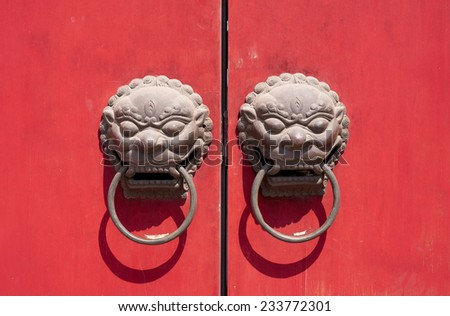 Antique Chinese lion door knocker on red door in Shanghai China - stock photo