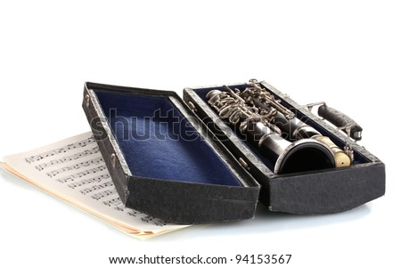 Antique clarinet in case and notebook with notes isolated on white - stock photo