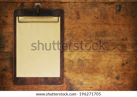 Antique clipboard on old grungy wooden surface, with plenty of copy space.  - stock photo