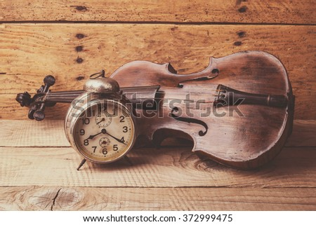 Antique clock and old violin over vintage wooden table - selective focus, copy space - stock photo