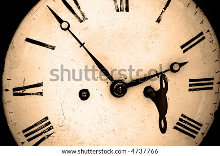Antique clock face with winder key in position, sepia toned. - stock photo