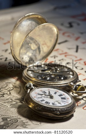 Antique clock on ancient book in Latin - stock photo